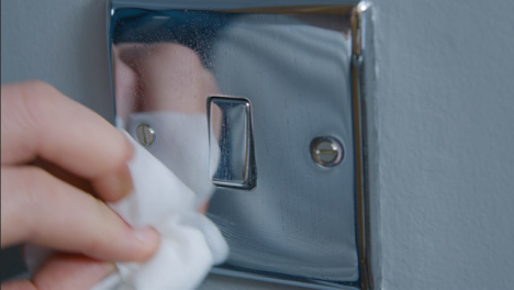 Sliding-Extreme-Close-Up-Shot-of-Male-Hand-Cleaning-a-Light-Switch-On-Wall