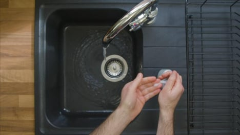 Top-Down-Shot-of-Male-Hands-Turning-On-Kitchen-Tap-and-Washing-with-Soap