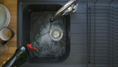 Top-Down-Shot-of-Male-Hands-Pouring-Washing-Liquid-into-Sink-Under-a-Running-Tap