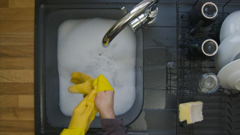 Top-Down-Shot-of-Male-Hands-Removing-Rubber-Gloves-After-Completing-Washing-Up