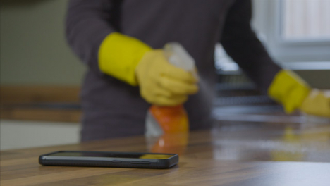Sliding-Close-Up-Shot-of-Phone-On-Kitchen-Surface-As-Adult-Cleans-In-Background