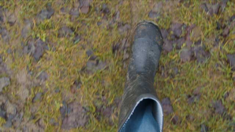 POV-Shot-Looking-Down-at-Boots-Walking-On-Muddy-Footpath