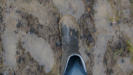 POV-Shot-Looking-Down-at-Boots-Walking-On-Wet-Muddy-Footpath