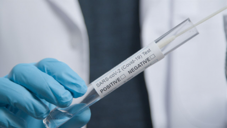 Close-Up-Shot-of-COVID-Test-Tube-as-médico-Professional-Places-Swab-In-It