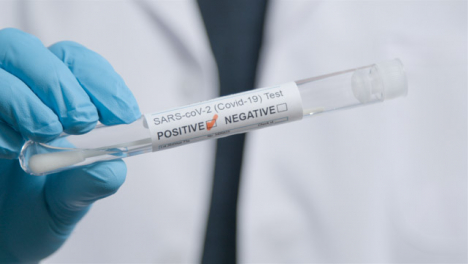 Close-Up-Shot-of-Doctor-Walking-Towards-Camera-Holding-Positive-COVID-Test-Tube-In-Hand