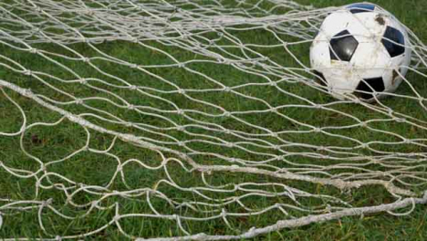 Medium-Shot-of-Soccer-Ball-Rolling-into-Goal-Net-Before-a-Foot-Rolls-It-Out