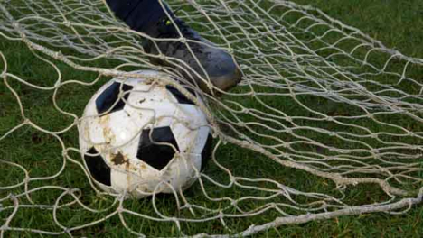 Medium-Shot-of-Soccer-Ball-Sitting-In-Goal-Net-Before-Foot-Rolls-It-Out