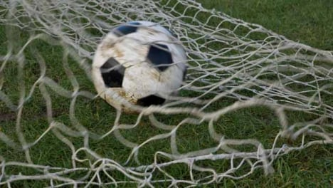 Medium-Shot-of-Soccer-Ball-Hitting-Goal-Net-Before-Rolling-Back-Out-of-Frame