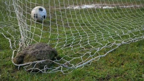 Close-Up-Shot-of-Rock-Holding-Down-Goal-Net-as-Soccer-Ball-Lands-In-Front-of-It