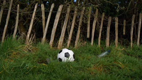 Medium-Shot-of-Soccer-Ball-Landing-In-Front-of-Dilapidated-Fence-Next-to-Litter