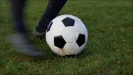 Defocused-Shot-of-Players-Boot-Kick-Stationary-Soccer-Ball-