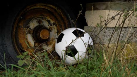 Close-Up-Shot-of-Soccer-Ball-Landing-Next-Rusted-Wheel-and-Concrete-Blocks