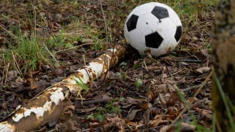 Medium-Shot-of-Soccer-Ball-Landing-Next-to-Rusted-Goal-Post-Laying-On-Floor