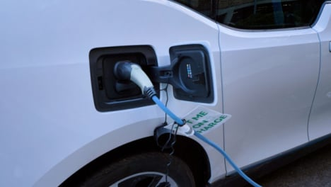 Tilting-Shot-Looking-Up-at-Charging-Cable-Plugged-into-Electric-Car-