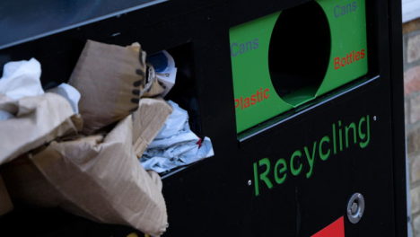 Handheld-Close-Up-Shot-of-Overflowing-Recycling-Bin-On-Street