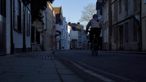Low-Angle-Shot-of-Cyclist-Riding-Down-an-Old-Street