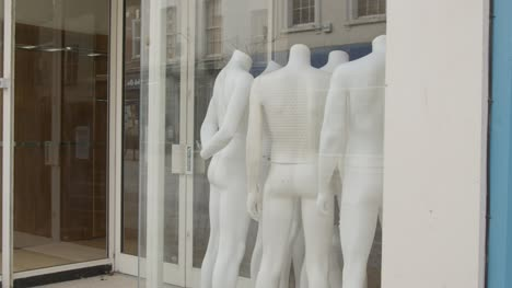 Tracking-Shot-Past-Shop-Window-Full-of-Disused-Mannequins-