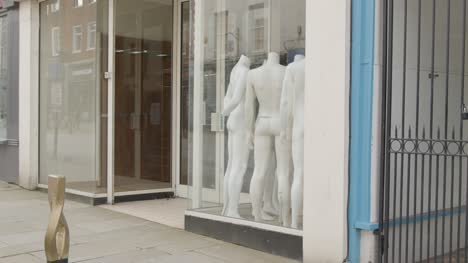 Tracking-Shot-Pulling-Away-from-Shop-Window-Full-of-Disused-Mannequins-