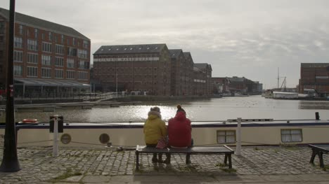 Wide-Shot-of-People-Sitting-On-Waterside-Bench-
