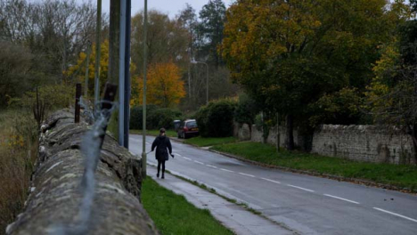 Wide-Shot-of-Young-Woman-Walking-Dog-Down-Country-Road