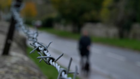 Close-Up-Shot-of-Barbed-Wire-Fence-with-Dog-Walker-In-Background