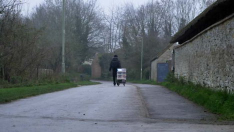 Wide-Shot-of-Person-Pulling-Sack-Truck-Down-Rural-Town-Footpath