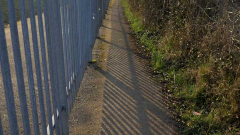 Tracking-Shot-Along-Footpath-Next-to-a-Metal-Fence