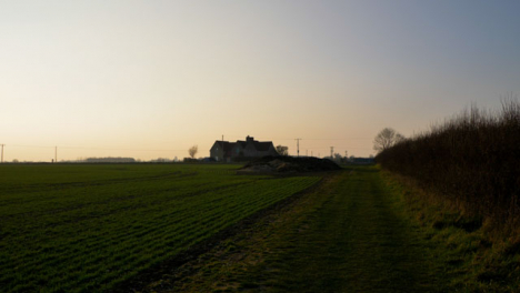 Tracking-Shot-Along-Field-Footpath-Leading-to-Farmhouse-