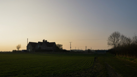 Tilting-Shot-Looking-Up-from-Puddle-to-Reveal-Farmhouse-at-Sunset