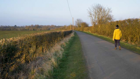 Panning-Shot-of-Person-Walking-Down-Countryside-Road