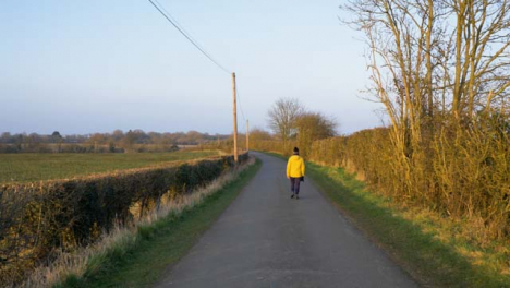 Tracking-Shot-Following-Person-Walking-Down-Countryside-Road