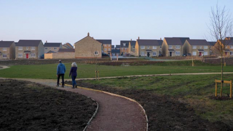 Tracking-Shot-Following-Couple-Walking-Along-Footpath-Leading-to-New-Housing-Area