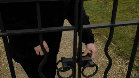 Close-Up-Shot-of-Womans-Hand-Opening-and-Closing-Iron-Gate-