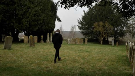 Wide-Shot-of-Young-Woman-Walking-Through-Rural-Graveyard-