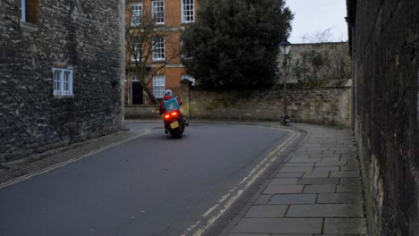 Tracking-Shot-Past-Wall-Revealing-Cyclist-and-Delivery-Scooter-
