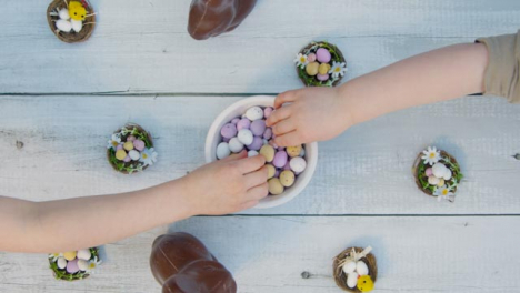 Overhead-Shot-of-Young-Children-s-Hands-Taking-Chocolate-Eggs-from-Bowl