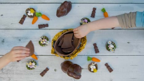 Overhead-Shot-of-Young-Children-s-Hands-Taking-Pieces-of-Chocolate-Egg-from-Table