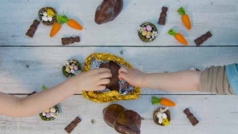 Overhead-Shot-of-Adult-and-Children-s-Hands-Taking-Last-Pieces-of-Chocolate-Egg-from-Table