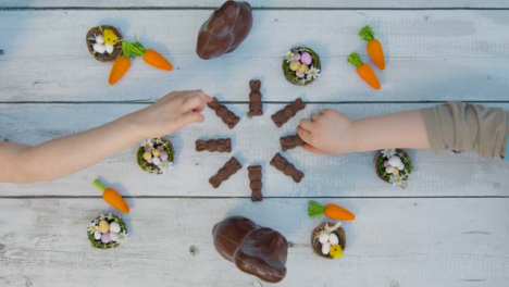 Overhead-Shot-of-Young-Children-s-Hands-Taking-Small-Chocolate-Bunnies-from-Table