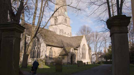 Wide-Shot-of-Elderly-Person-Pushing-Buggy-Past-Church