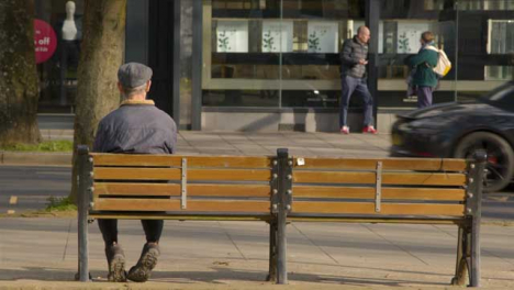 Long-Shot-of-Elderly-Person-Sitting-On-Street-Bench