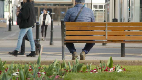 Low-Angle-Shot-of-Person-Sitting-On-Street-Bench