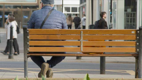 Medium-Shot-of-Person-Sitting-On-Street-Bench