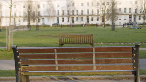 Close-Up-Shot-of-Empty-Park-Bench-as-People-Walk-In-Background