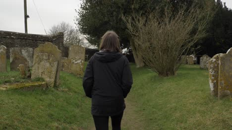 Tracking-Shot-Following-Young-Woman-Walking-Along-Graveyard-Footpath