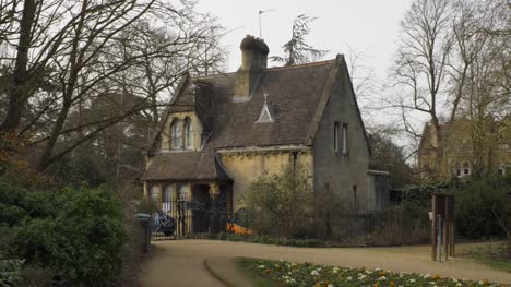 Tracking-Shot-Approaching-Quaint-Cottage-Building-On-Edge-of-Park-