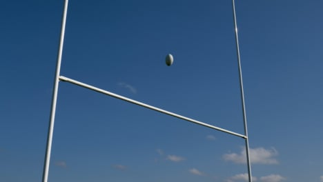 Low-Angle-Shot-Looking-Up-at-Rugby-Posts-as-Rugby-Ball-Flies-Over