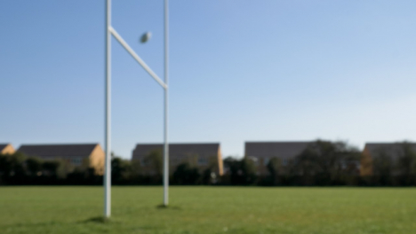 Defocused-Wide-Shot-of-Rugby-Ball-Flying-Through-Rugby-Posts