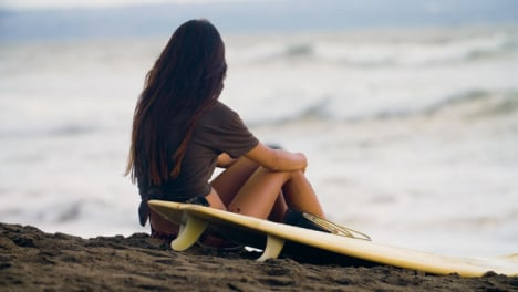 Long-Shot-of-Young-Woman-Sitting-On-Beach-