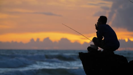 Handheld-Long-Shot-of-Fisherman-Silhouetted-Against-Sunset